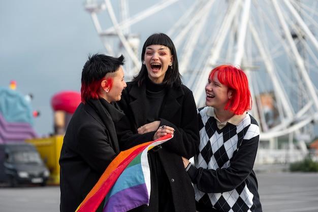 Szczęśliwa grupa niebinarnych ludzi z flagą lgbt