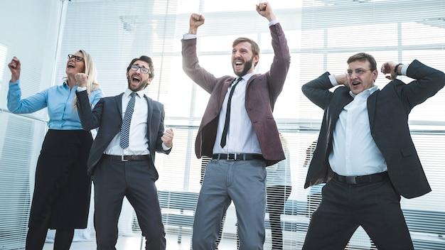 Szczęśliwa grupa pracowników pokazująca swój sukces .photo z kopią przestrzeni