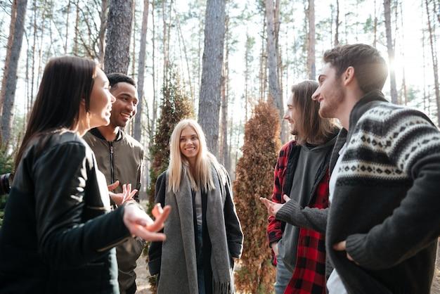Szczęśliwa grupa przyjaciele stoi outdoors w lesie