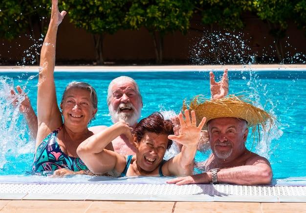 Szczęśliwa grupa przyjaciół bawiących się na basenie razem ze światłem słonecznym i przezroczystą wodą