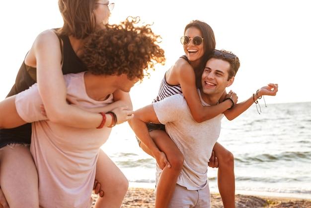 Szczęśliwa grupa przyjaciół kochających pary spacery na świeżym powietrzu na plaży, zabawy