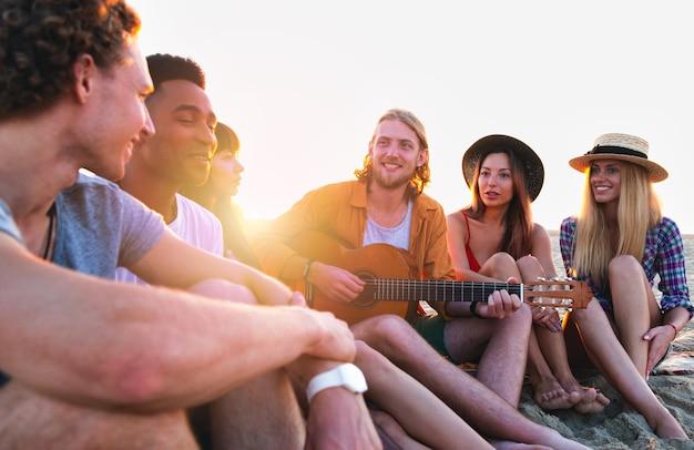 Szczęśliwa grupa przyjaciół o imprezie na plaży