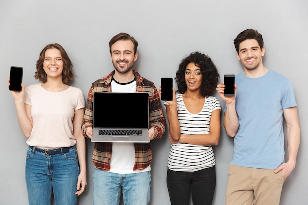 Szczęśliwa grupa przyjaciół pokazuje wyświetlacze telefonów komórkowych i laptopa.