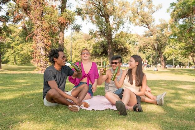 Szczęśliwa grupa przyjaciół spędzających razem słoneczny dzień w parku