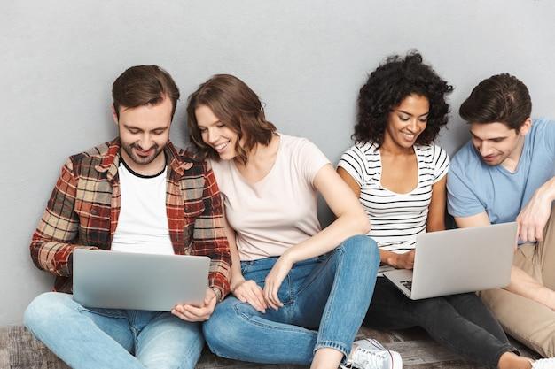 Szczęśliwa grupa przyjaciół za pomocą laptopów.