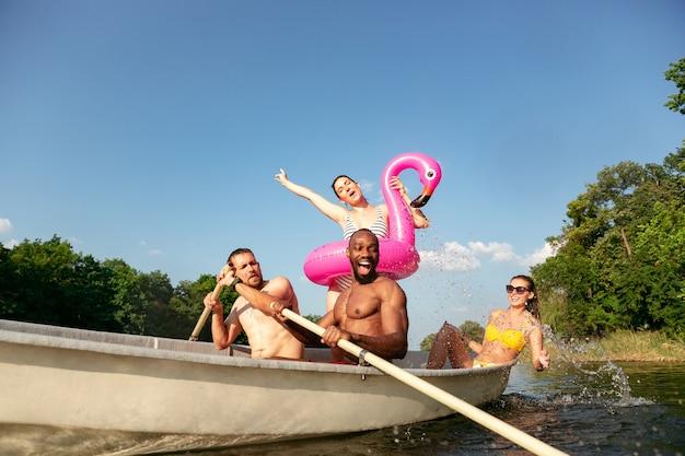 Szczęśliwa grupa przyjaciół, zabawy podczas śmiechu i pływania w rzece. radosnych mężczyzn i kobiet w strojach kąpielowych w łodzi na brzegu rzeki w słoneczny dzień. lato, przyjaźń, kurort, koncepcja weekendu.