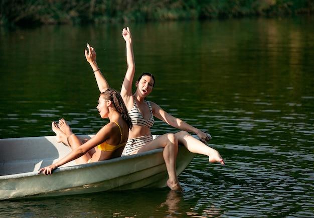 Szczęśliwa grupa przyjaciół, zabawy podczas śmiechu, pluskania wody i pływania w rzece