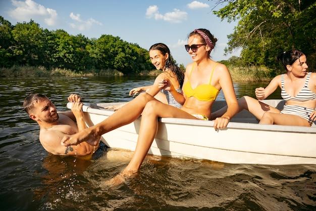 Szczęśliwa grupa przyjaciół, zabawy, śmiechu i kąpieli w rzece