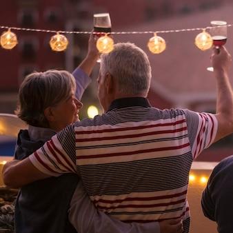 Szczęśliwa grupa starych starszych kaukaskich przyjaciół świętuje razem nocą, brzęcząc i wznosząc toast czerwonym winem - koniec awaryjnego lokdown koronawirusa i przyjaźni ludzie znów za darmo