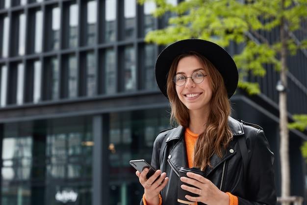 Szczęśliwa hipster dziewczyna trzyma papierowy kubek z pysznym napojem kofeinowym, używa telefonu komórkowego do wykonywania połączeń, sms-ów online, nosi kapelusz