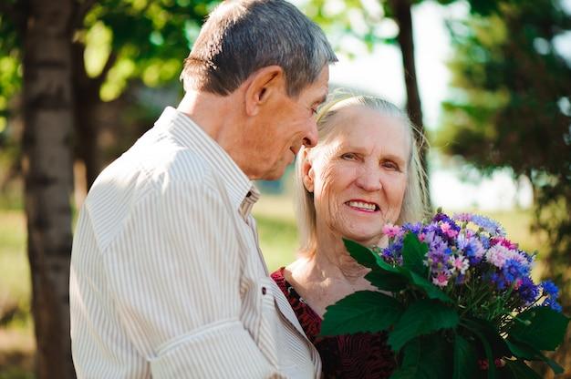 Szczęśliwa i bardzo stara para ono uśmiecha się w parku na słonecznym dniu.