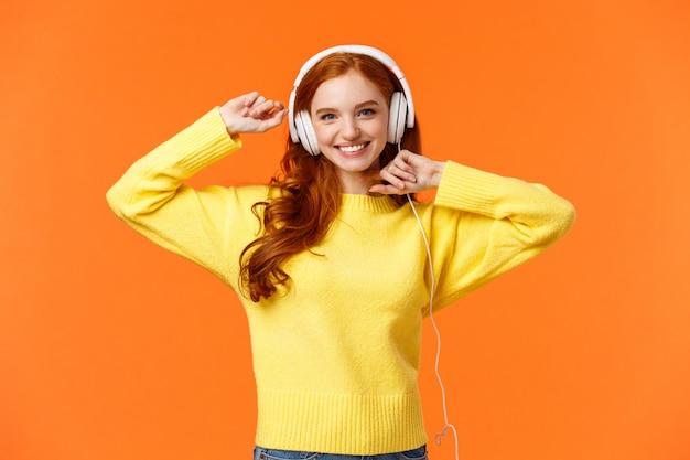 Szczęśliwa i beztroska podekscytowana rudowłosa dziewczyna jak jej nowe słuchawki