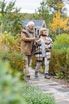 Szczęśliwa i czuła starsza para w ciepłym casuawlear poruszająca się wąską drogą między krzewami i drzewami, dyskutując o przyrodzie