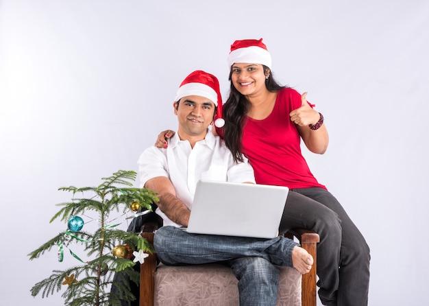 Szczęśliwa i młoda para indyjska na kanapie korzystająca z laptopa podczas świętujących boże narodzenie