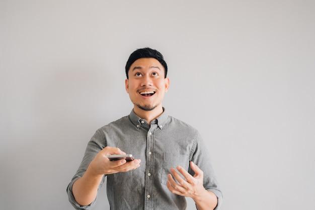 Szczęśliwa i no! no! twarz azjatycki mężczyzna use smartphone na odosobnionym szarym tle