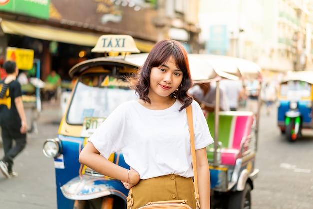 Szczęśliwa i piękna azjatycka kobieta podróżuje przy khao sarn drogą, tajlandia