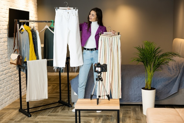 Szczęśliwa i piękna blogerka, influencerka, pokazuje ubrania obserwującym, aby mogli je sprzedawać w sklepie online