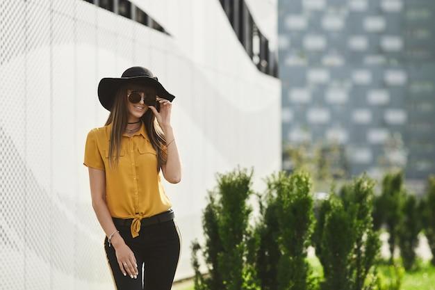 Szczęśliwa i piękna brunetka modelka o idealnym ciele w żółtej bluzce i modnym czarnym kapeluszu, dostosowująca swoje stylowe okulary przeciwsłoneczne, uśmiecha się i pozująca na zewnątrz