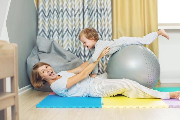 Szczęśliwa i piękna mama i dziecko, rodzina razem trenują piłkę gimnastyczną