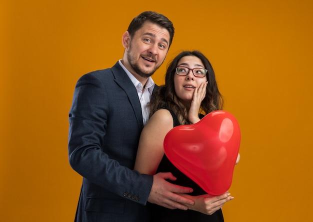 Szczęśliwa i piękna para mężczyzna i kobieta z czerwonym balonem w kształcie serca, obejmując świętuje walentynki nad pomarańczową ścianą