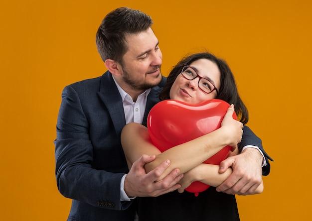 Szczęśliwa I Piękna Para Mężczyzna I Kobieta Z Czerwonym Balonem W Kształcie Serca, Obejmując świętuje Walentynki Nad Pomarańczową ścianą Darmowe Zdjęcia
