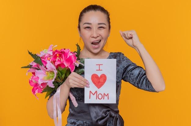 Szczęśliwa i podekscytowana azjatycka kobieta trzymająca kartkę z życzeniami i bukiet kwiatów z okazji międzynarodowego dnia kobiet zaciskająca pięść stojącą nad pomarańczową ścianą