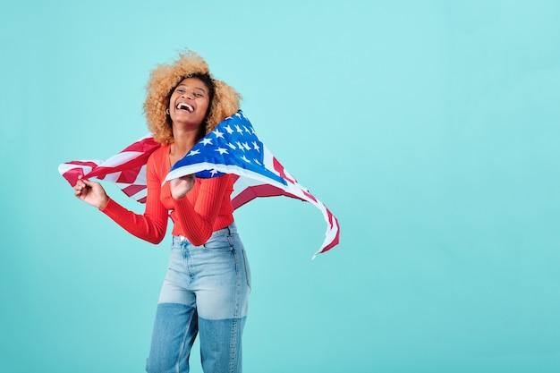 Szczęśliwa i podekscytowana kobieta afro z amerykańską flagą, stojąca na odosobnionym tle. koncepcja obchodów dnia niepodległości.