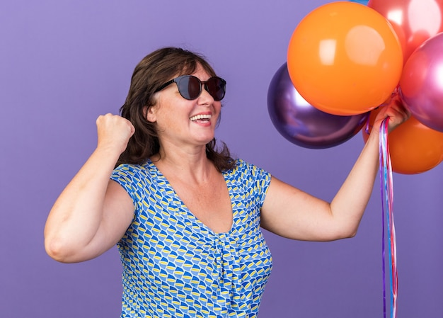 Szczęśliwa i podekscytowana kobieta w średnim wieku trzymająca pęk kolorowych balonów zaciskająca pięść świętująca przyjęcie urodzinowe stojąca nad fioletową ścianą