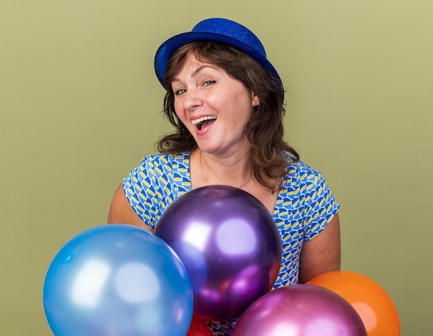 Szczęśliwa i podekscytowana kobieta w średnim wieku w imprezowym kapeluszu z wiązką kolorowych balonów bawiących się