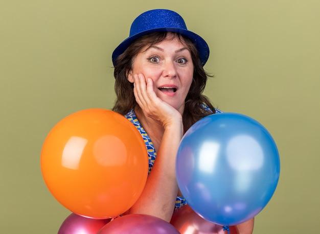 Szczęśliwa i podekscytowana kobieta w średnim wieku w imprezowym kapeluszu z wiązką kolorowych balonów