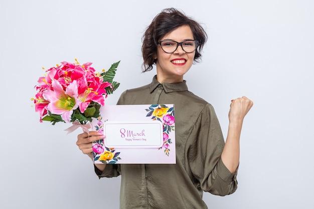Szczęśliwa i podekscytowana kobieta z krótkimi włosami trzymająca kartkę z życzeniami i bukiet kwiatów patrząc na kamerę zaciskając pięść świętującą międzynarodowy dzień kobiet 8 marca stojąc na białym tle