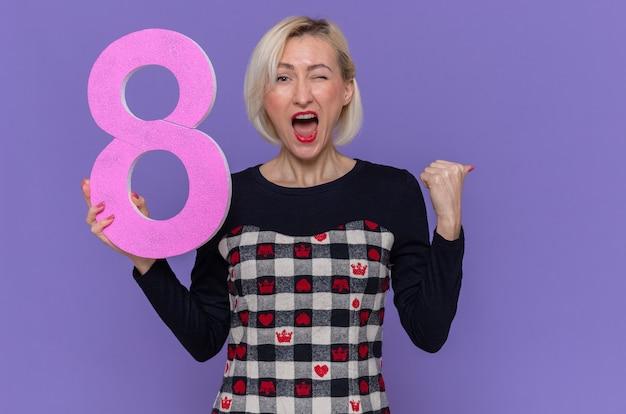 Szczęśliwa i podekscytowana młoda kobieta trzyma numer osiem zaciskając pięść krzycząc