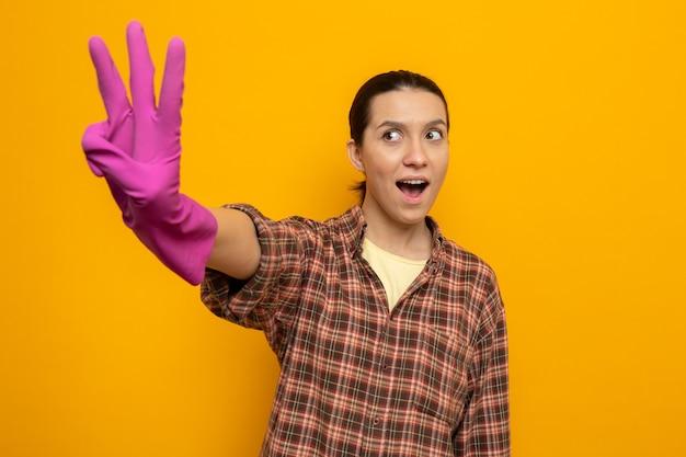 Szczęśliwa i podekscytowana młoda sprzątaczka w zwykłych ubraniach w gumowych rękawiczkach pokazująca numer trzy z palcami stojącymi nad pomarańczową ścianą