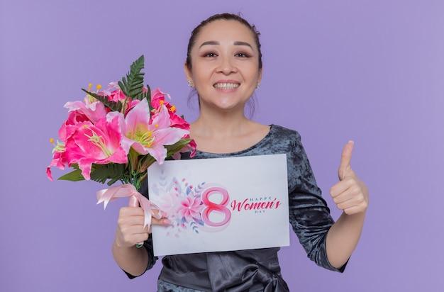 Szczęśliwa i pozytywna azjatycka kobieta matka trzyma bukiet kwiatów i kartkę z życzeniami z okazji międzynarodowego dnia kobiet marsz