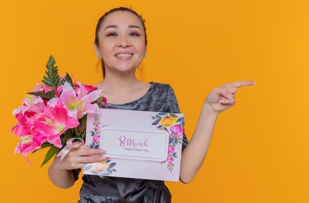 Szczęśliwa i pozytywna azjatycka kobieta matka trzyma kartkę z życzeniami i bukiet kwiatów z okazji międzynarodowego dnia kobiet marsz
