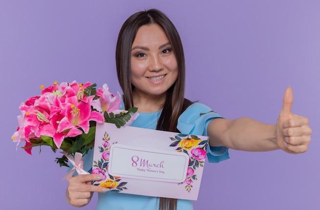Szczęśliwa i pozytywna azjatycka kobieta trzyma kartkę z życzeniami i bukiet kwiatów