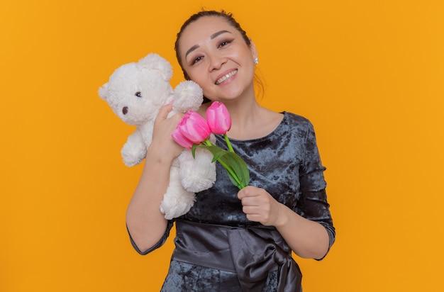 Szczęśliwa i pozytywna azjatycka kobieta trzymająca bukiet różowych tulipanów i misia uśmiechnięta wesoło świętująca międzynarodowy dzień kobiet stojąca nad pomarańczową ścianą