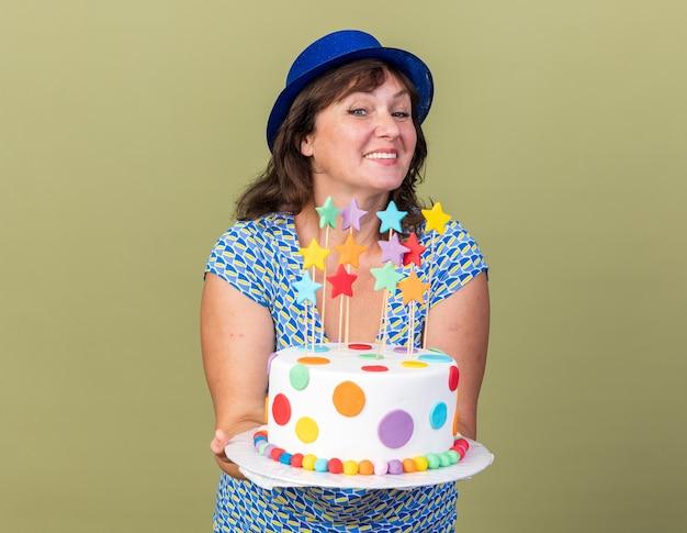 Szczęśliwa i pozytywna kobieta w średnim wieku w imprezowym kapeluszu trzymająca tort urodzinowy uśmiechnięta radośnie świętująca przyjęcie urodzinowe stojące nad zieloną ścianą