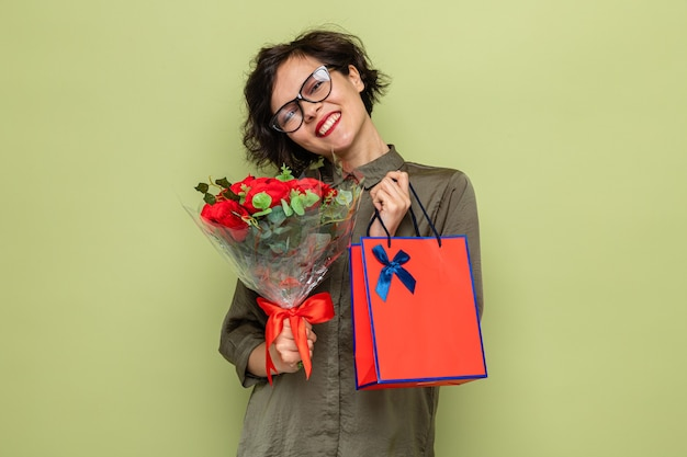Szczęśliwa i pozytywna kobieta z krótkimi włosami trzyma bukiet kwiatów i papierową torbę z prezentami, uśmiechając się radośnie z okazji międzynarodowego dnia kobiet