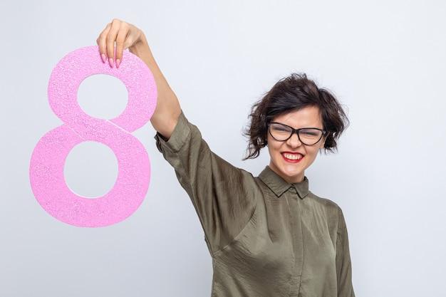 Szczęśliwa i pozytywna kobieta z krótkimi włosami trzymająca numer osiem z kartonu, patrząc w kamerę, uśmiechnięta radośnie świętująca międzynarodowy dzień kobiet 8 marca stojąca na białym tle