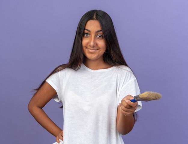 Szczęśliwa i pozytywna młoda dziewczyna w białej koszulce trzymająca pędzel, patrząca na kamerę, uśmiechnięta radośnie stojąca na niebieskim tle