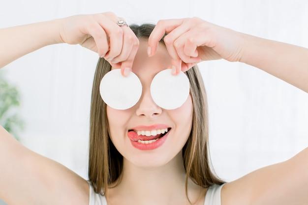 Szczęśliwa i pozytywna młoda piękna kobieta z otwartymi ramionami zakrywa jej oczy wacikami i pokazuje jęzor na lekkim tle. koncepcja pielęgnacji skóry i urody