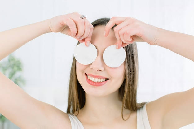 Szczęśliwa i pozytywna młoda piękna kobieta z otwartymi ramionami zakrywa jej oczy z wacikami i ono uśmiecha się na lekkim tle. koncepcja pielęgnacji skóry i urody