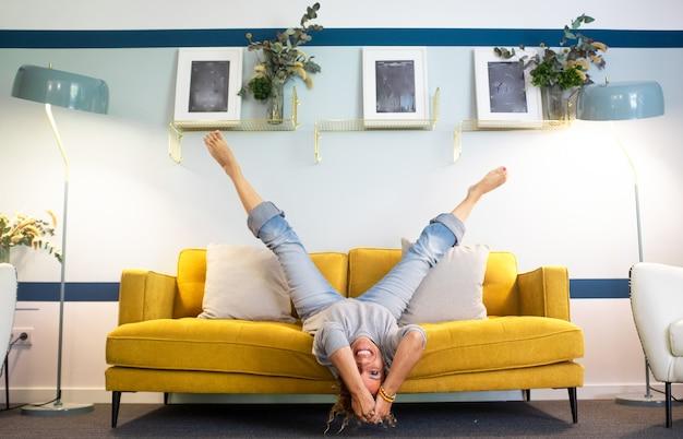 Szczęśliwa i radosna dorosła kobieta położyła się na kanapie w odwróconej pozycji z nogami w górę i głową w dół uśmiechając się i bawiąc w domu - w średnim wieku młoda dama aktywny tryb życia dużo śmiejąc się na kanapie