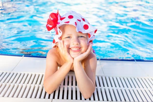 Szczęśliwa i radosna dziewczynka przy basenie latem w panamie i uśmiechnięta, koncepcja podróży i rekreacji