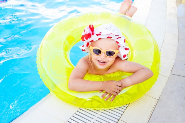 Szczęśliwa i radosna dziewczynka w pobliżu basenu z nadmuchiwanym żółtym kółkiem i okularami przeciwsłonecznymi w letnich uśmiechach