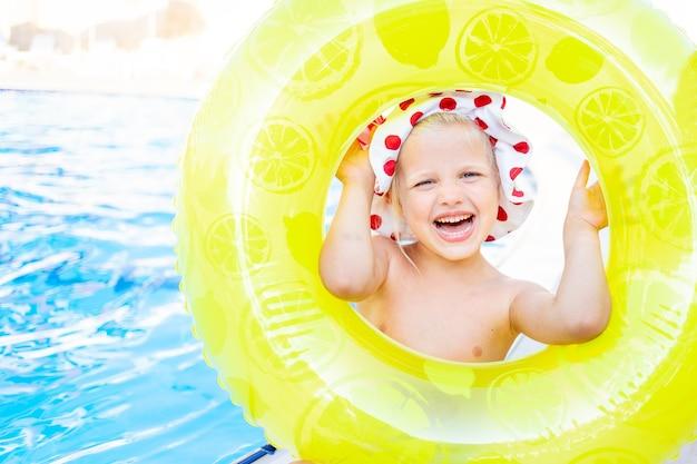 Szczęśliwa i radosna dziewczynka wygląda latem z nadmuchiwanego żółtego koła w pobliżu basenu i uśmiecha się, koncepcja podróży i rekreacji