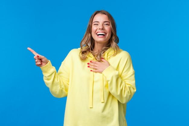 Szczęśliwa i rozbawiona ładna blond kobieta w żółtej bluzie z kapturem, śmiejąca się głośno z czegoś zabawnego w lewym górnym rogu niebieskiej ściany, uśmiechnięta