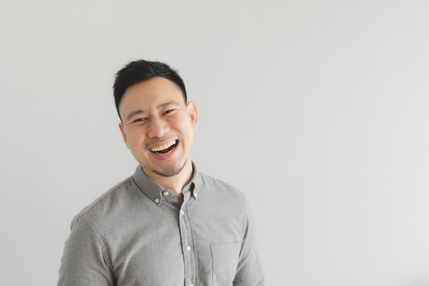 Szczęśliwa i roześmiana twarz zwykłego człowieka w szarej koszuli. koncepcja uroczego śmiechu.