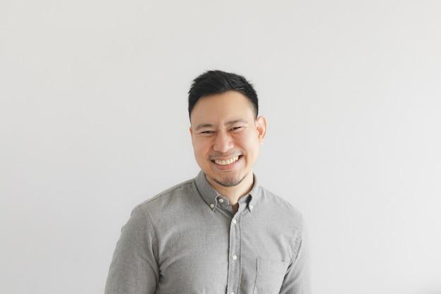 Szczęśliwa i roześmiana twarz zwykłego mężczyzny w szarej koszuli. koncepcja uroczego śmiechu.